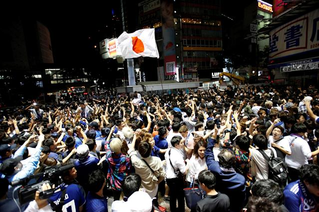 Soccer fans and pedestrians exchange high fives in praise of Japan's soccer team players near a diagonal crosswalk after World Cup Group H soccer match Japan vs Senegal, at Shibuya district in Tokyo, Japan June 25, 2018. REUTERS/Issei Kato TPX IMAGES OF THE DAY