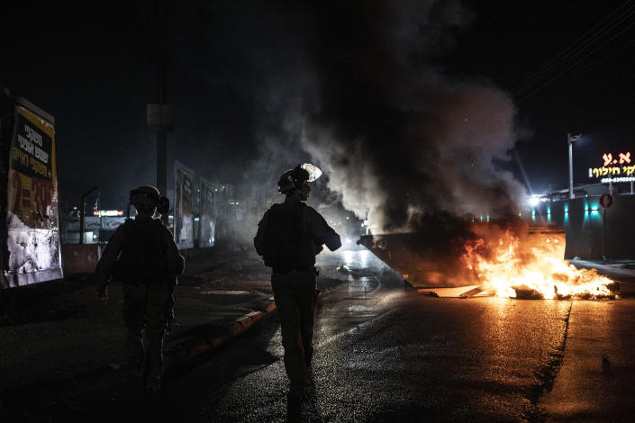 Israeli police patrol during clashes between Arabs, police and Jews, in the mixed town of Lod, central Israel, Wednesday, May 12, 2021. As rockets from Gaza streaked overhead, Arabs and Jews fought each other on the streets below. Rioters torched vehicles, a restaurant and a synagogue in one of the worst spasms of communal violence that Israel has seen in years. (AP Photo/Heidi Levine)