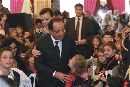 French President Francois Hollande and his companion Valerie Trierweiler are greeted by children as they arrive at the Christmas party at the Elysee Palace, in Paris, December 18, 2013. REUTERS/Philippe Wojazer
