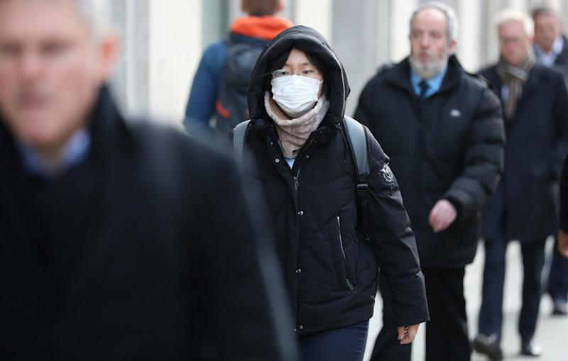 A pedestrian wears a face mask whilst walking along High Holborn in central London (PA)