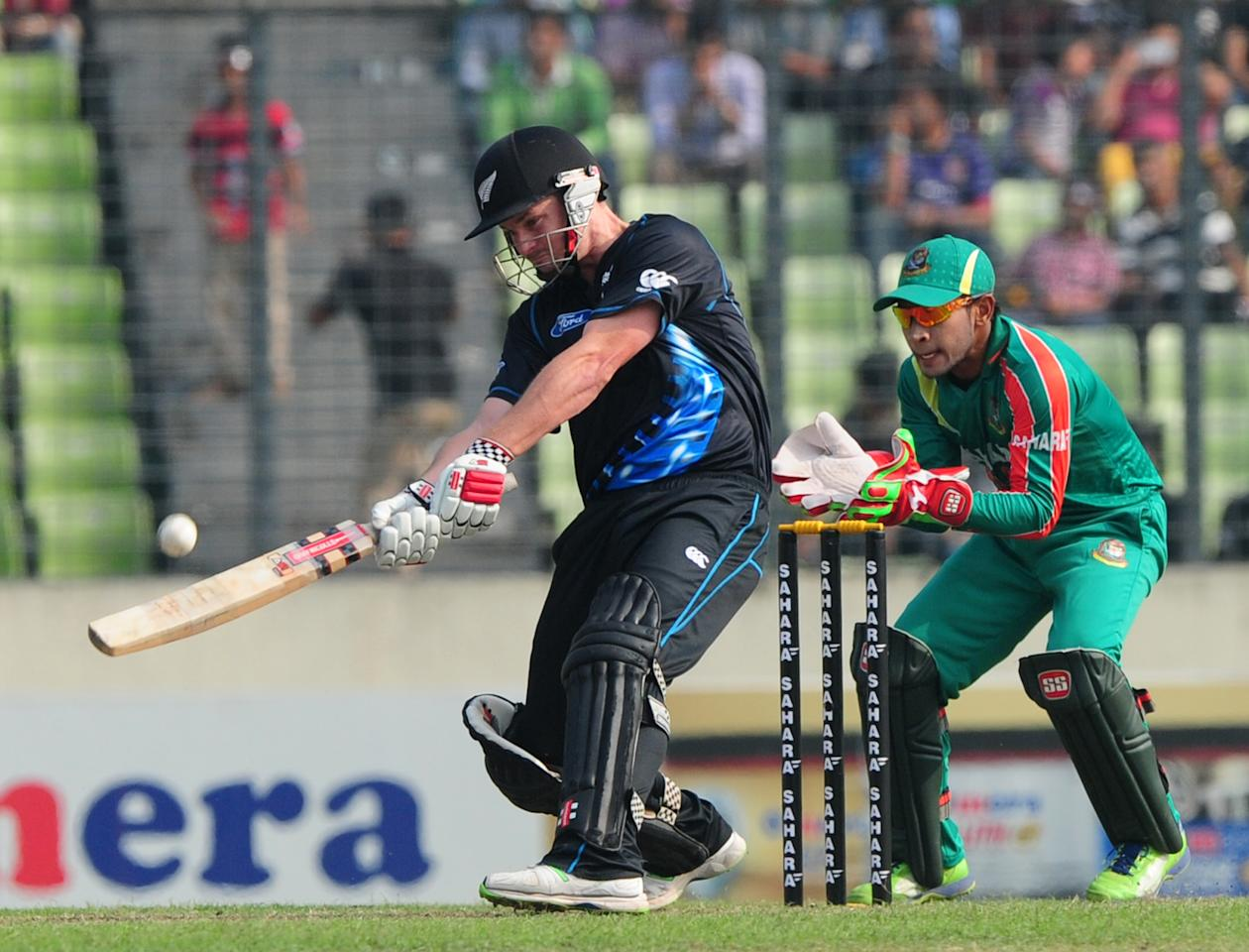 New Zealand batsman Colin Munro (L) plays a shot as Bangladesh captain Mushfiqur Rahim looks on during the T20 match between Bangladesh and Zew Zealand at the Sher-e-Bangla National Cricket Stadium in Dhaka on November 6, 2013. AFP PHOTO/ Munir uz ZAMAN        (Photo credit should read MUNIR UZ ZAMAN/AFP/Getty Images)