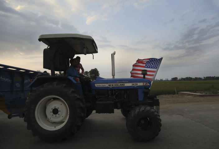 An Indian farmer drives his tractor with a U.S. flag across wheat fields in Moga district of Indian state of Punjab, Friday, March 12, 2021. India's water crisis looms over the agrarian crisis that has been brewing for decades. And at its heart is a policy conundrum: India has been subsidizing the cultivation of rice in northern India, but these are thirsty crops that have depleted the ground water. (AP Photo/Manish Swarup)