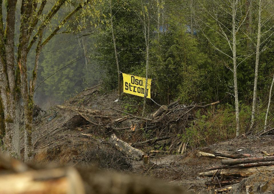"In this Wednesday, April 16, 2014, photo, a sign that reads ""Oso Strong"" is shown on the edge of the debris field of the massive deadly mudslide that hit the community of Oso, Wash., on March 22, 2014. When President Barack Obama arrives for a visit Tuesday, April 22, he'll find a haunting wasteland. He'll also find lingering signs of perseverance and gratitude. (AP Photo/Ted S. Warren)"