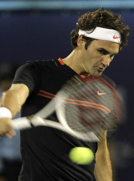 Roger Federer of Switzerland returns the ball to Michael Llodra of France during the Emirates Dubai ATP Tennis Championships in Dubai, United Arab Emirates, Tuesday, Feb. 28, 2012. (AP Photo/Hassan Ammar)