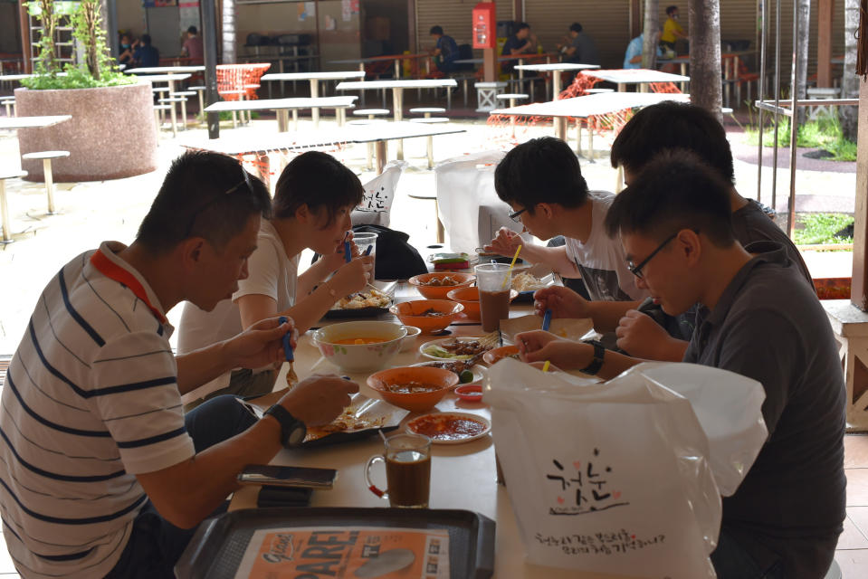 A group of five people have lunch together at the Newton Food Center Friday, June 19, 2020, in Singapore. Singaporeans can now wine and dine at restaurants, work out at gyms and get together with five people or less after most lockdown restrictions were lifted Friday. (AP Photo/YK Chan)