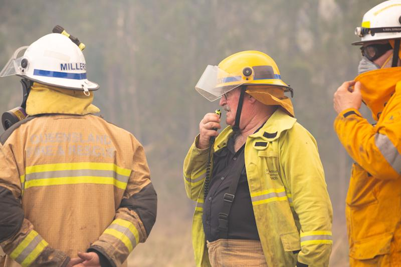 Three firefighters are seen near fires at Lake Cooroibah Road in Noosa.