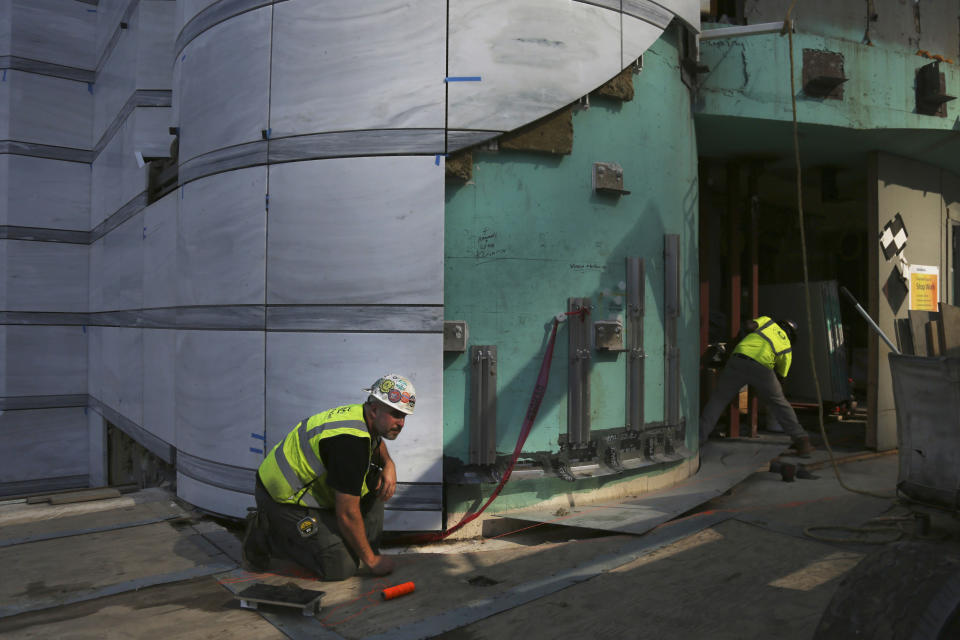 Andrew Resch, left, an MG McGrath Inc. project superintendent for the construction of St. Nicholas Greek Orthodox Church and National Shrine, makes a measurement at its base on Friday, Aug. 27, 2021, in New York. The shrine will have a ceremonial lighting on the eve of the 20th anniversary of the Sept. 11, 2001 attacks, while the interior is slated for completion next year. (AP Photo/Jessie Wardarski)