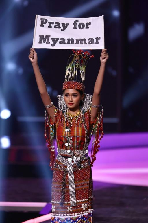 """Miss Myanmar Thuzar Wint Lwin (pictured May 13, 2021) wore an outfit beaded in traditional Burmese patterns and held up a sign that said, """"Pray for Myanmar"""" during the national costume portion of the Miss Universe pageant"""