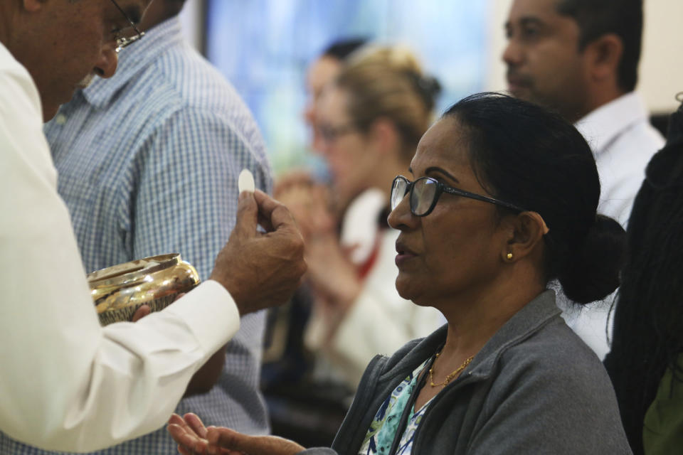 In this Sunday, Jan. 20, 2019 photo, a parishioner at St. Mary's Catholic Church prepares to take Holy Communion during Mass in Dubai, United Arab Emirates. The Catholic Church's parishioners in the UAE come from around the world and will offer an international welcome to Pope Francis on his visit Feb. 3 through Feb. 5, the first by a pontiff to the Arabian Peninsula, the birth place of Islam. The Catholic Church believes there are some 1 million Catholics in the UAE today. (AP Photo/Jon Gambrell)