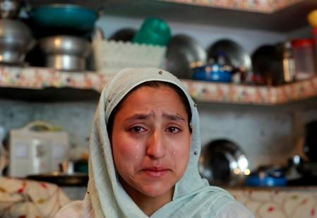 Woman weeps inside her house after her household goods were allegedly damaged by Indian security forces following clashes between protesters and the security forces on Friday evening, in Srinagar