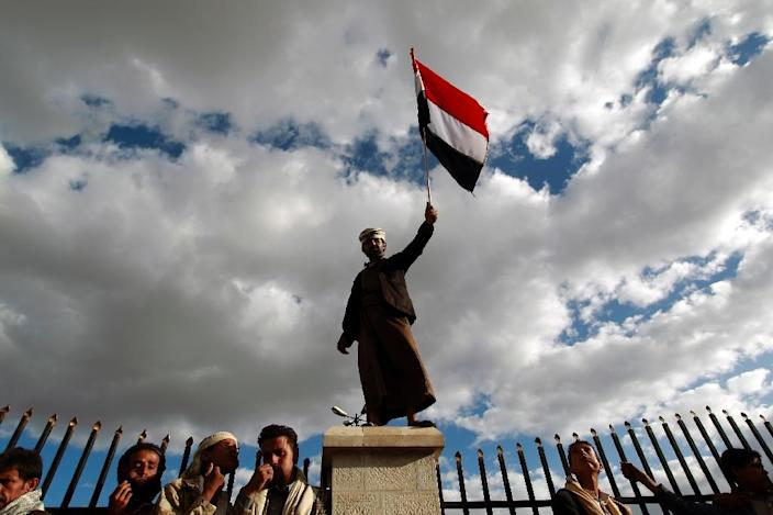 A Shiite-Huthi supporter holds a national flag during a protest in Sanaa against military operations carried out by the Saudi-led coalition and over claims that Saudi Arabia was denying Yemenis the right to attend hajj, September 11, 2015 (AFP Photo/Mohammed Huwais)
