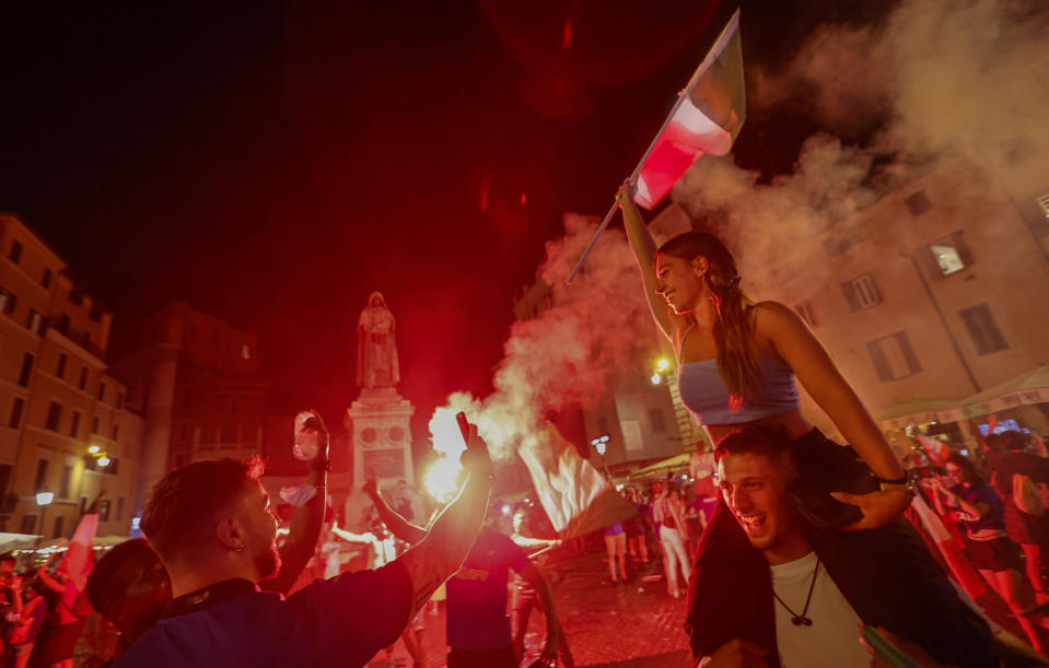 Fans celebrate in Rome, Monday, July 12, 2021, after Italy beat England to win the Euro 2020 soccer championships in a final played at Wembley Stadium in London. The score was 3-2 in a penalty shootout after a 1-1 draw. (AP Photo/Riccardo De Luca)