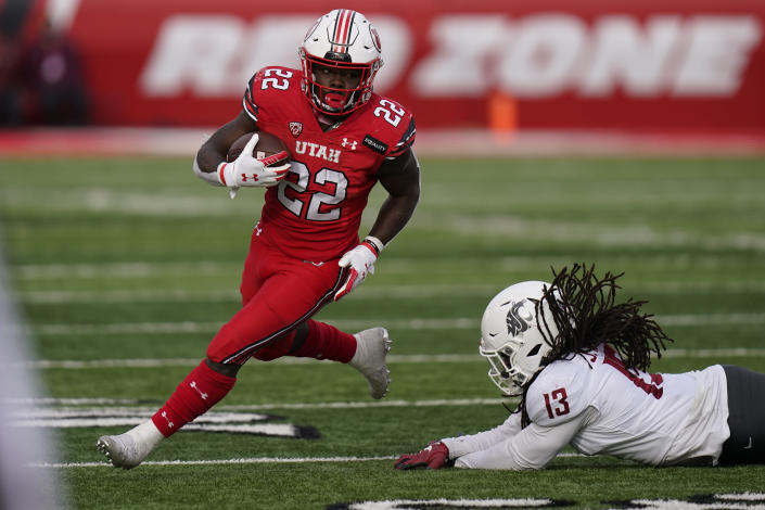 FILE - In this Dec. 19, 2020, file photo, Utah running back Ty Jordan (22) runs for a score as he eludes a tackle by Washington State linebacker Jahad Woods (13) during the second half of an NCAA college football game, in Salt Lake City. Jordan, a star freshman running back for the University of Utah who grew up in the Dallas area, has died, school officials announced Saturday, Dec. 26. Authorities in Texas and Utah have not released details about the circumstances of the Jordan's death. (AP Photo/Rick Bowmer, File)