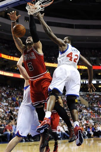 Chicago Bulls' Carlos Boozer (9) has his shot blocked by Philadelphia 76ers' Elton Brand (42) during the first half of Game 4 in a first-round NBA basketball playoff series, Sunday, May 6, 2012, in Philadelphia. (AP Photo/Michael Perez)