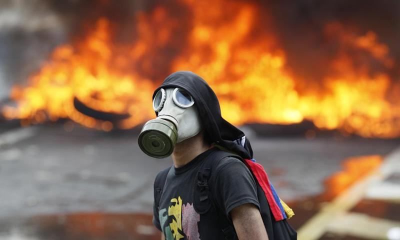 An anti-government protester in front of burning barricade in Caracas.