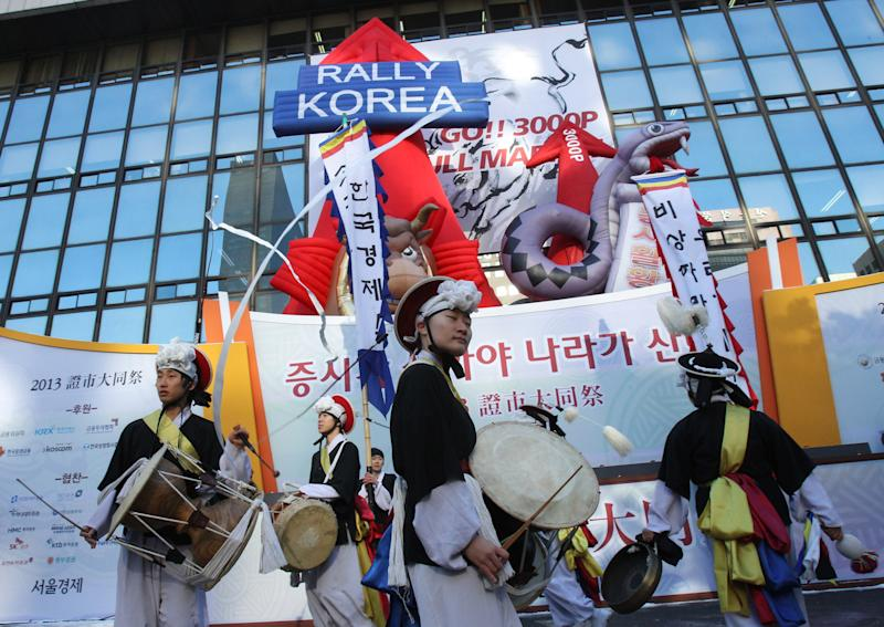 CORRECTS THE DATE - South Korean dancers in traditional costumes beat their drums during opening ceremony of the Year 2013 trading outside the Seoul Stock Exchange Wednesday, Jan. 2, 2013. The benchmark Korea Composite Stock Price Index (KOSPI) started up 16.69 points, or 0.84 percent, at 2, 013.74. (AP Photo/Ahn Young-joon)