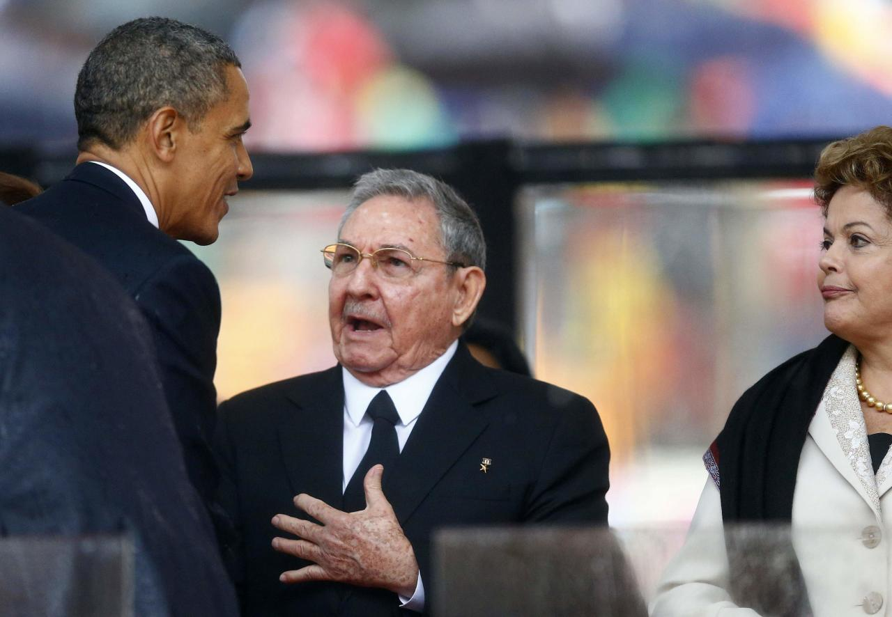 U.S. President Barack Obama (L) greets Cuban President Raul Castro (C) before giving his speech, as Brazil's President Dilma Rousseff looks on, at the memorial service for late South African President Nelson Mandela at the First National Bank soccer stadium, also known Soccer City, in Johannesburg in this December 10, 2013 file photo. REUTERS/Kai Pfaffenbach/Files (SOUTH AFRICA - Tags: POLITICS OBITUARY)