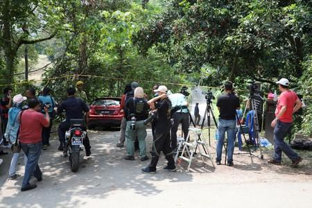 Members of the media wait at the entrance to the Dusun Resort, where 15-year-old Irish girl Nora Anne Quoirin went missing in Seremban
