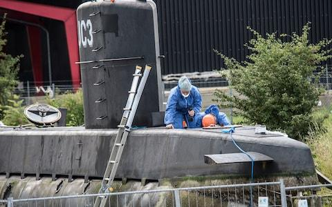police technicians on board the home-made submarine UC3 Nautilus on a pier in Copenhagen harbour - Credit: AP