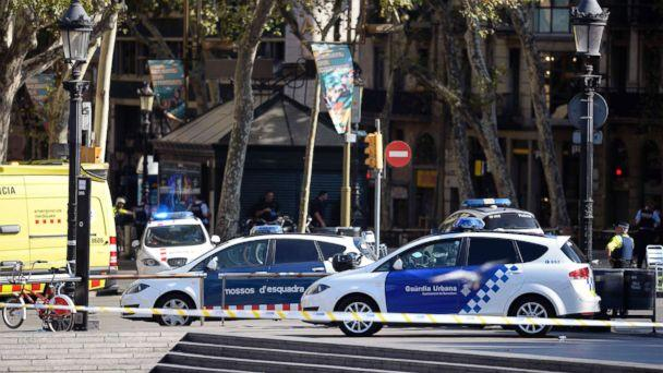 PHOTO: Policemen stand next to vehicles in a cordoned off area after a van ploughed into the crowd, injuring several persons on the Rambla in Barcelona, Aug. 17, 2017. (Josep Lago/AFP/Getty Images)