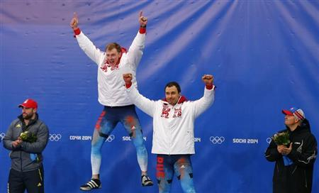Russia's Zubkov and Voevoda celebrate on the podium at the flower ceremony after winning the two-man bobsleigh event at the 2014 Sochi Winter Olympics