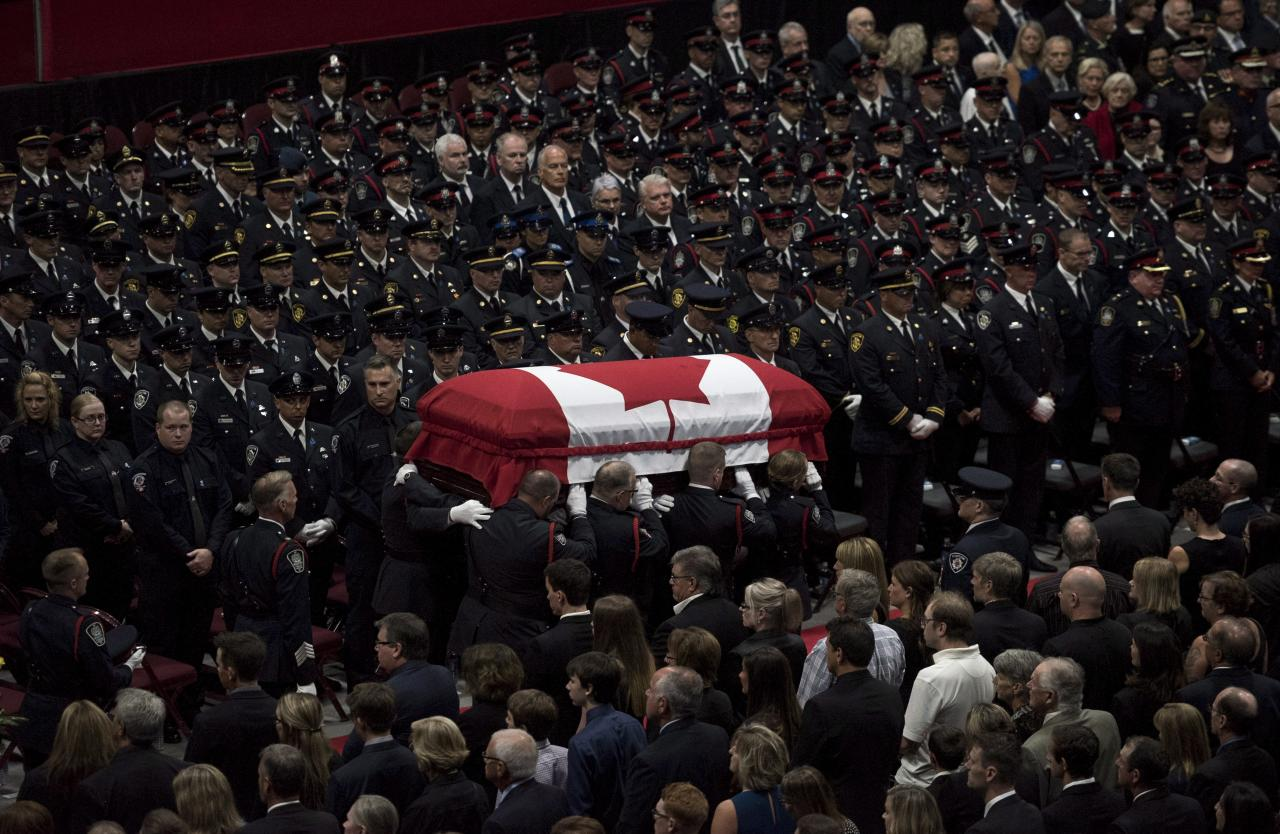 <p>The flag-draped casket of slain Fredericton police officer Cst. Robb Costello is carried past members of the Fredericton Police department, family, and friends during a regimental funeral for Cst. Costello and Cst. Sara Burns on in Fredericton on Saturday, Aug. 18, 2018. (Photo from The Canadian Press/Darren Calabrese) </p>
