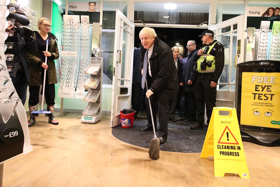 Prime Minister Boris Johnson helps with the clean up at an opticians as he visits Matlock, Derbyshire to view the flooding.