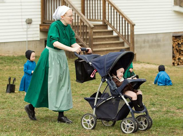 Emma Miller pushes her son in a stroller outside the schoolhouse in Bergholz, Ohio, Tuesday, April 9, 2013. Miller, along with three other women and a man from this tight-knit community in rural eastern Ohio, will enter prison on Friday, April 12, joining nine already behind bars on hate crimes convictions for hair- and beard-cutting attacks against fellow Amish. (AP Photo/Scott R. Galvin)