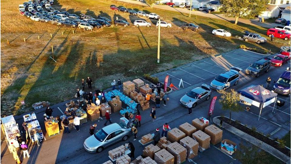 Volunteers load boxes of food assistance into cars at the Share Your Christmas food distribution event sponsored by the Second Harvest Food Bank of Central Florida