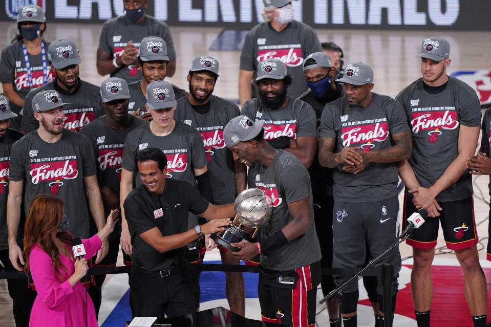 Miami Heat head coach Erik Spoelstra, center left, hands the Eastern Conference trophy to Bam Adebayo (13) as they celebrate their NBA conference final playoff basketball game win over the Boston Celtics with the Eastern Final trophy Sunday, Sept. 27, 2020, in Lake Buena Vista, Fla. (AP Photo/Mark J. Terrill)