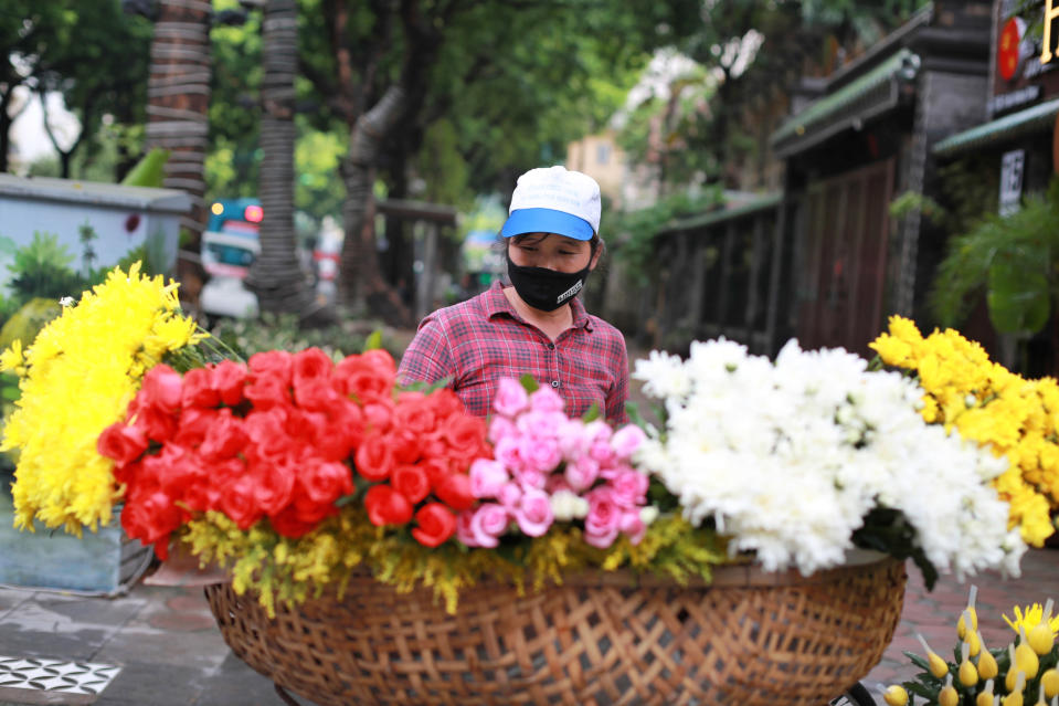 A flower vender wearing a face mask to protect against the coronavirus waits for customers in Hanoi, Vietnam, Monday, Aug. 3, 2020. Vietnam has tightened travel and social restrictions after the country's death toll of COVID-19 to six. (AP Photo/Hau Dinh)