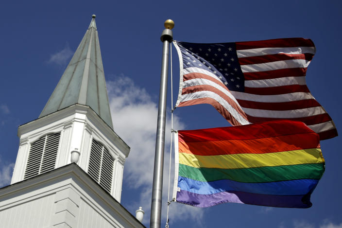 FILE - In this April 19, 2019 file photo, a gay pride rainbow flag flies along with the U.S. flag in front of the Asbury United Methodist Church in Prairie Village, Kan. Conservative leaders within the United Methodist Church unveiled plans Monday, March 1, 2021 to form a new denomination, the Global Methodist Church, with a doctrine that does not recognize same-sex marriage. The move could hasten the long-expected breakup of the UMC, America's largest mainline Protestant denomination, over differing approaches to LGBTQ inclusion. (AP Photo/Charlie Riedel, File)