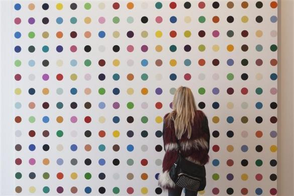 "A woman looks at a painting by Damien Hirst at a preview for his exhibition ""Damien Hirst: The Complete Spot Paintings 1986-2011"" at the Gagosian Gallery in central London, January 12, 2012."
