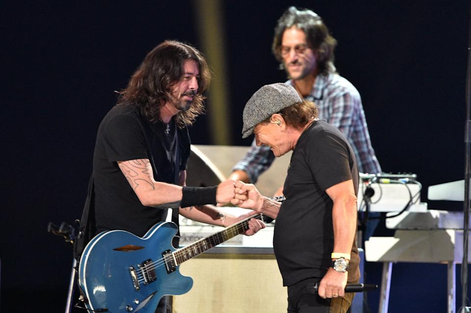 """AC/DC's Brian Johnson, right, joins Dave Grohl, left, and Foo Fighters for a rendition of the AC/DC classic """"Back in Black"""" at """"Vax Live"""" at SoFi Stadium in Inglewood, Calif., on May 2, 2021."""