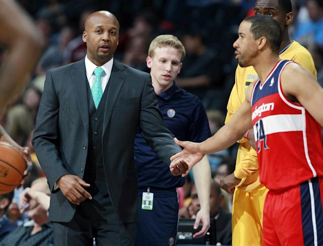 Denver Nuggets head coach Brian Shaw, left, greets Washington Wizards guard Andre Miller as he takes floor in the first quarter of an NBA basketball game on Sunday, March 23, 2014, in Denver. Shaw and Miller argued over playing time for Miller during a game on New Year's Day, which ended up in Miller being traded to Washington. (AP Photo/David Zalubowski)