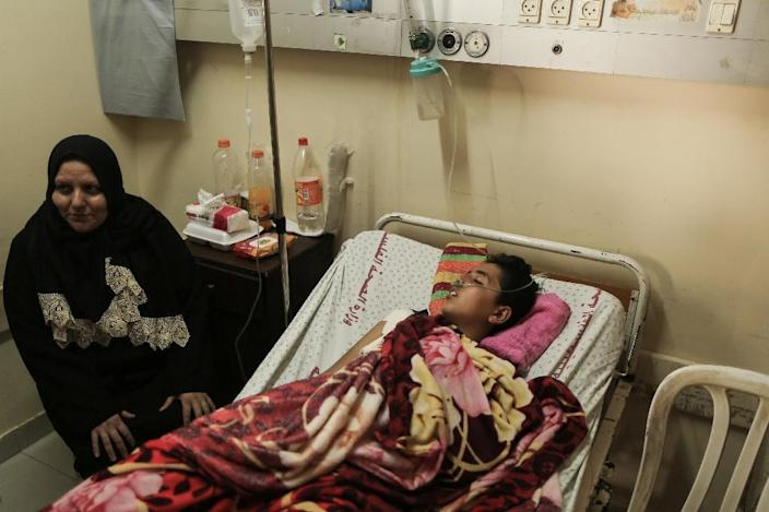 A Palestinian youth wounded at the Israel-Gaza border lies on a bed next to his mother at Shifa Hospital in Gaza City on April 1, 2018 (AFP Photo/MAHMUD HAMS)
