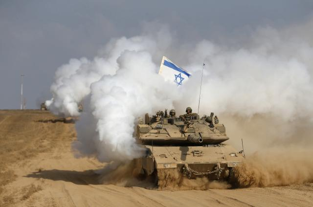 An Israeli soldier gestures from atop a tank after crossing the border back into Israel August 5, 2014. Israel pulled its ground forces out of the Gaza Strip on Tuesday and started a 72-hour ceasefire with Hamas mediated by Egypt as a first step towards negotiations on a more enduring end to the month-old war. REUTERS/Baz Ratner (ISRAEL - Tags: POLITICS CONFLICT CIVIL UNREST MILITARY TPX IMAGES OF THE DAY)