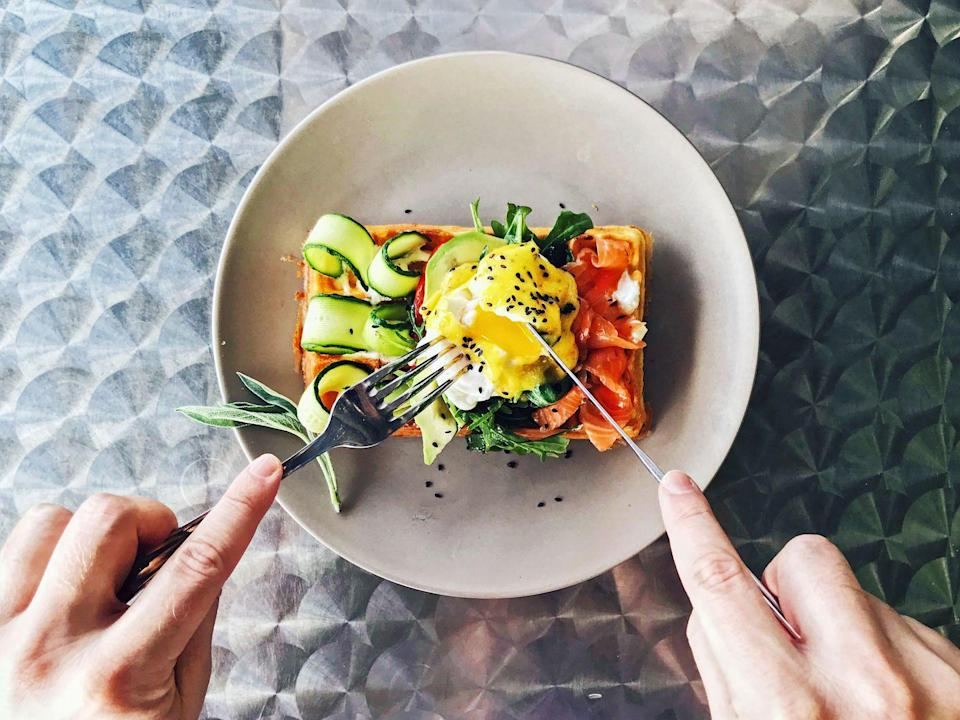 """<p>As a more preventative measure, opt for a breakfast that is high in protein and low in carbs, and then aim for a smaller lunch. <a href=""""https://www.sciencedirect.com/science/article/pii/S1878450X17300045?via%3Dihub"""" rel=""""nofollow noopener"""" target=""""_blank"""" data-ylk=""""slk:Research"""" class=""""link rapid-noclick-resp"""">Research</a> shows that a well-balanced breakfast delivers energy slowly over the course of the morning, rather than all at once, which could lead to a later slump. A breakfast high in carbs (like pancakes) can lead to a <a href=""""https://www.hsph.harvard.edu/nutritionsource/carbohydrates/carbohydrates-and-blood-sugar/"""" rel=""""nofollow noopener"""" target=""""_blank"""" data-ylk=""""slk:spike in blood sugar,"""" class=""""link rapid-noclick-resp"""">spike in blood sugar,</a> which can result in a loss of energy later (like at 3 p.m.). </p><p><a href=""""https://www.medicalnewstoday.com/articles/323379#why-do-people-feel-tired-after-eating"""" rel=""""nofollow noopener"""" target=""""_blank"""" data-ylk=""""slk:Research"""" class=""""link rapid-noclick-resp"""">Research</a> also shows that eating a large lunch can cause your body to produce serotonin, which can leave you feeling tired. Try to keep your lunch on the small side and filled with energizing foods, like nuts, eggs, or beans.</p>"""