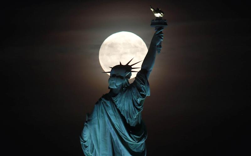 The full Harvest Moon rises behind the Statue of Liberty in New York City - Corbis News