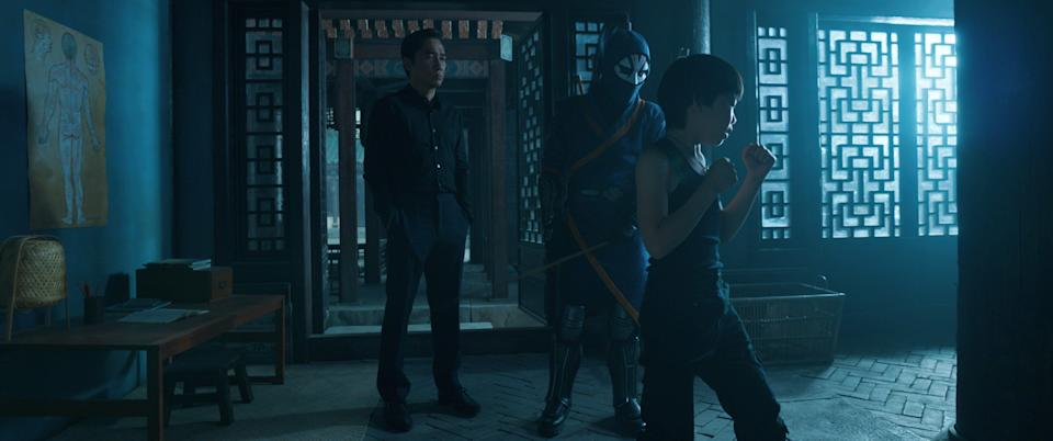 """Wenwu (Tony Leung, far left) watches as Death Dealer trains his son Shang-Chi (Jayden Tianyi Zhang) in in """"Shang-Chi and the Legend of the Ten Rings."""""""