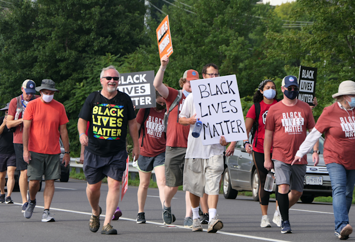The Rev. Keith Mannes, in a Black Lives Matter T-shirt, walks with protesters.