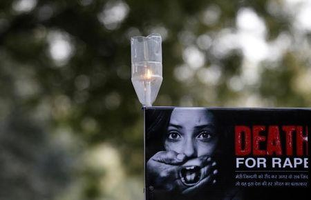 A candle is seen on a placard during a protest in New Delhi December 29, 2012.  REUTERS/Adnan Abidi/Files