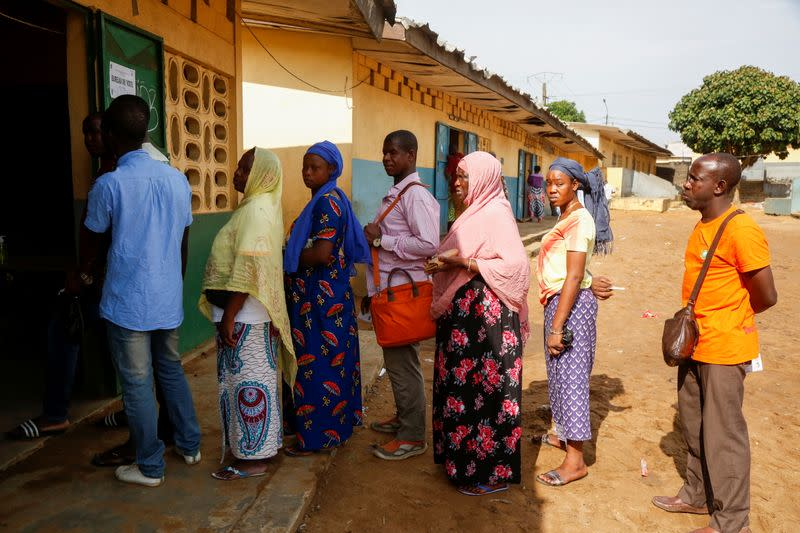 People wait in front of a polling station during the legislative election in Abidjan