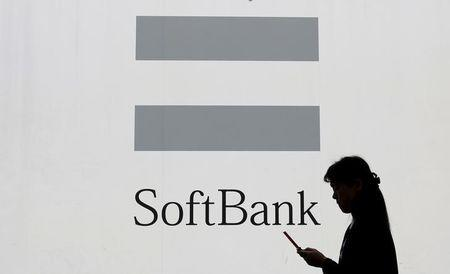 A woman using a mobile phone walks past the logo of SoftBank Corp in Tokyo