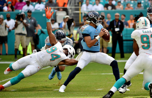 <p>Tennessee Titans quarterback Marcus Mariota (8) throws a pass as Miami Dolphins defensive end Robert Quinn (94) has his facemask pulled on by Tennessee Titans offensive tackle Taylor Lewan (77) during the first half at Hard Rock Stadium. Mandatory Credit: Steve Mitchell-USA TODAY Sports </p>
