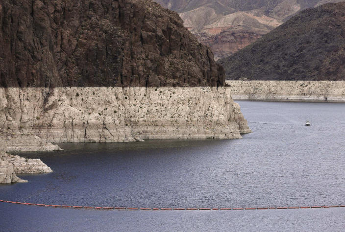 FILE - This Tuesday, April 16, 2013 file photo shows a bathtub ring marking the high water line as a recreational boat approaches Hoover Dam along Black Canyon on Lake Mead near Boulder City, Nev. A two-decade-long dry spell that has parched much of the western United States is turning into one of the deepest megadroughts in the region in more than 1,200 years, and about half of this historic drought can be blamed on man-made global warming, according to a study released Thursday, April 16, 2020 in the journal Science. (AP Photo/Julie Jacobson)