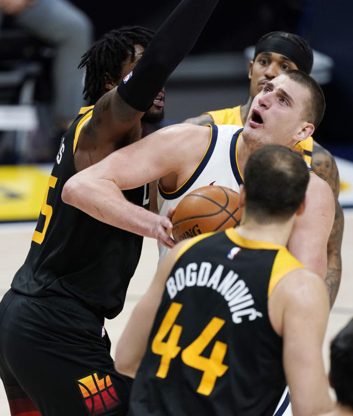 Denver Nuggets center Nikola Jokic, center, navigates to the rim through Utah Jazz forward Bojan Bogdanovic, front, center Derrick Favors, back left, and guard Jordan Clarkson in the second half of an NBA basketball game Sunday, Jan. 31, 2021, in Denver. (AP Photo/David Zalubowski)