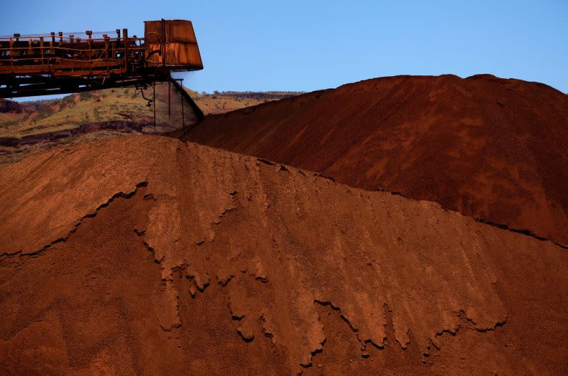 FILE PHOTO: A stacker unloads iron ore onto a pile at a mine located in the Pilbara region of Western Australia