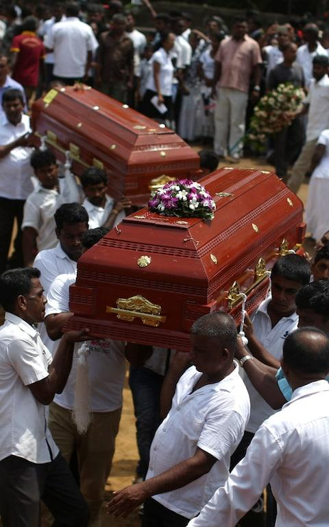 Mourners carry the coffins of victims during Tuesday's memorial ceremony - Credit: ATHIT PERAWONGMETHA/REUTERS