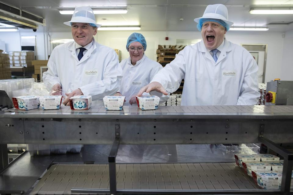 TOPSHOT - Britain's Prime Minister Boris Johnson (R) and Conservative MP George Eustice (L) react during a visit to Cornish Clotted Cream manufacturer
